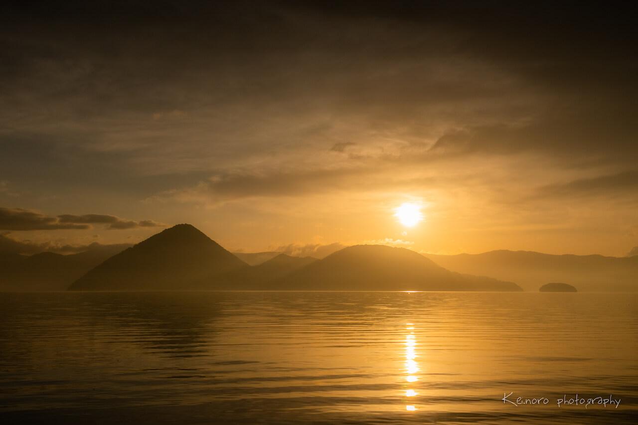 5月清晨在月浦所捕捉到的洞爺湖日出。據說從冬季到春季之間,湖水的透明度較高,尤其風平浪靜的時候,可以欣賞到日出的光線如道路般,美麗地倒映在湖面上。©Noro Keiichi