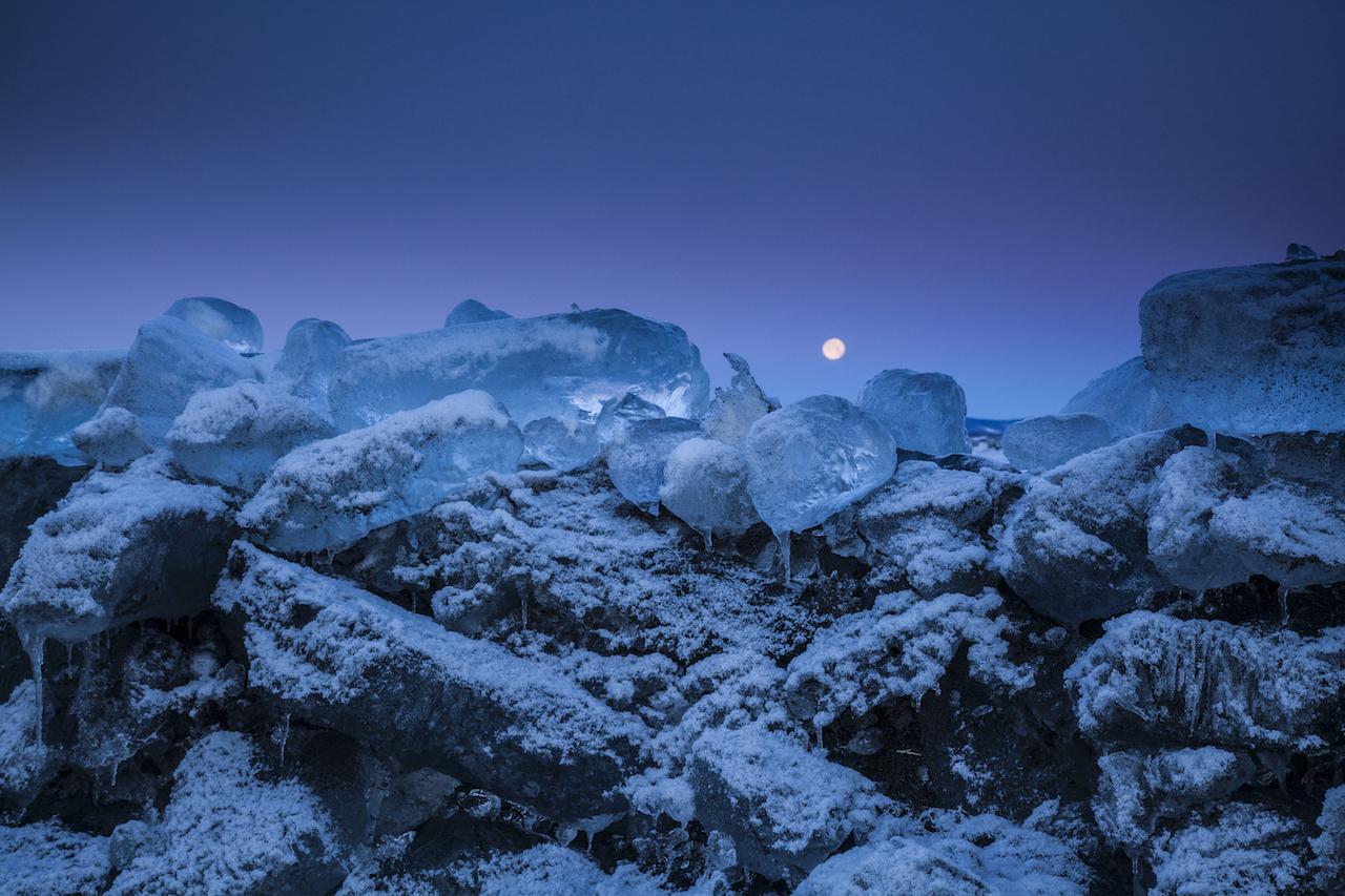 1月下旬,太陽升起前的黎明時分,滿月逐漸沒入地平線的一端。隨著滿潮退去,大塊的冰之寶石也隨之浮現。是早起的人才能遇見的美景。Ⓒ岸本日出雄