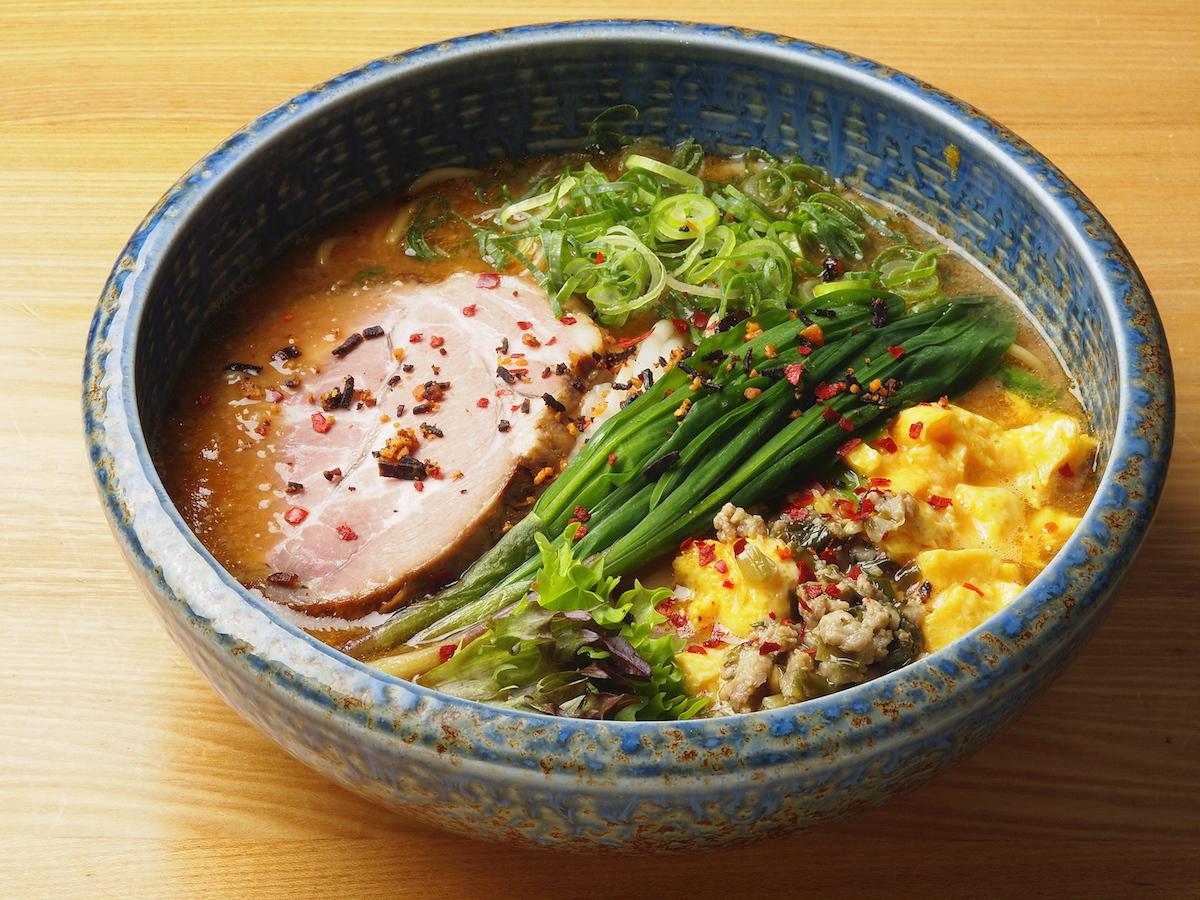 在加入了行者葫(又稱山蒜,是一種主要生長在北海道的山菜)的湯頭上,再放入以些許鹽調味的滑嫩炒蛋,成為獨一無二的絕妙組合,這就是「拉麵札幌 一粒庵(ラーメン札幌 一粒庵)」的招牌──「元氣滿分味噌拉麵DX」。