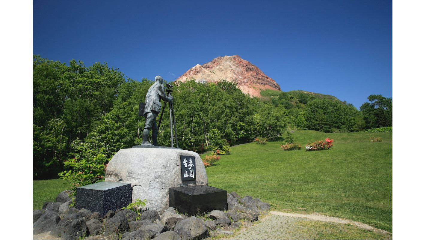 被指定為「特別天然記念物(nationally protected species)」的昭和新山山腳下,建有和山共存的三松正夫的紀念銅像。©spo/a.collectionRF /amanaimages